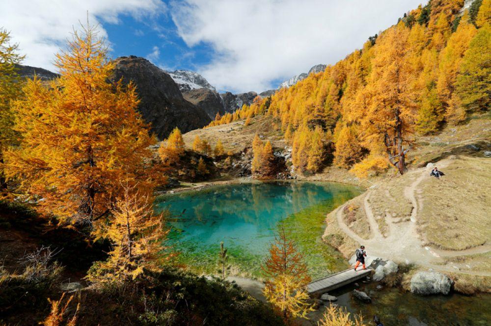 12 октября. Путешественники наслаждаются теплым осенним днем возле озера Блё в Швейцарии.