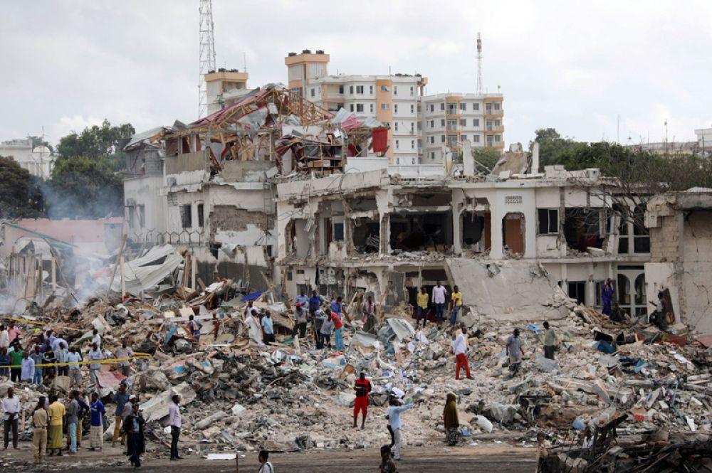 Полиция и мирные жители собираются на месте взрыва на улице КМ4 в районе Ходан в Могадишо.