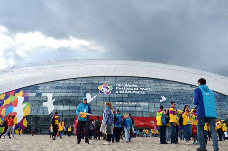 Участники и волонтеры XIX Всемирного фестиваля молодежи и студентов у Ледового дворца «Большой» в Олимпийском парке в Сочи.