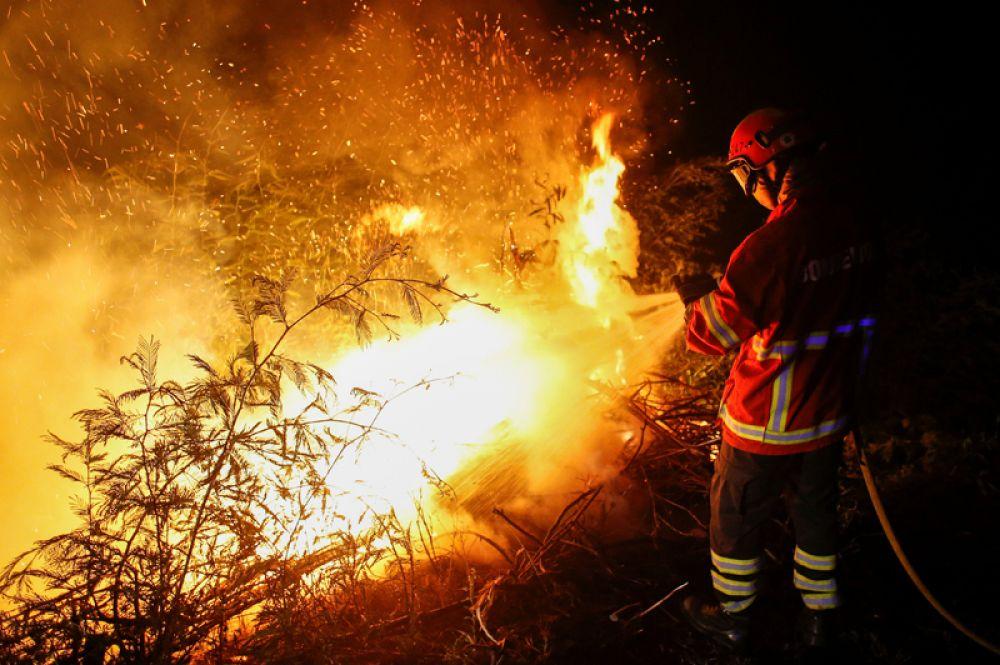 Пожарный тушит огонь около города Лоуса в Португалии.