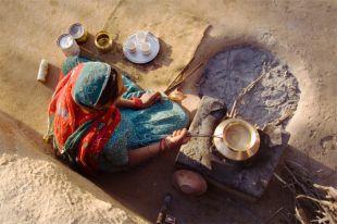 Индийцы готовят чай в железном чайнике на открытом огне.