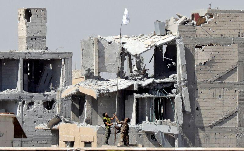 Бойцы «Сирийских демократических сил» поднимают белый флаг возле комплекса Национальной больницы.