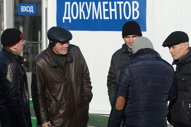 Посетители многофункционального миграционного центра в Москве.