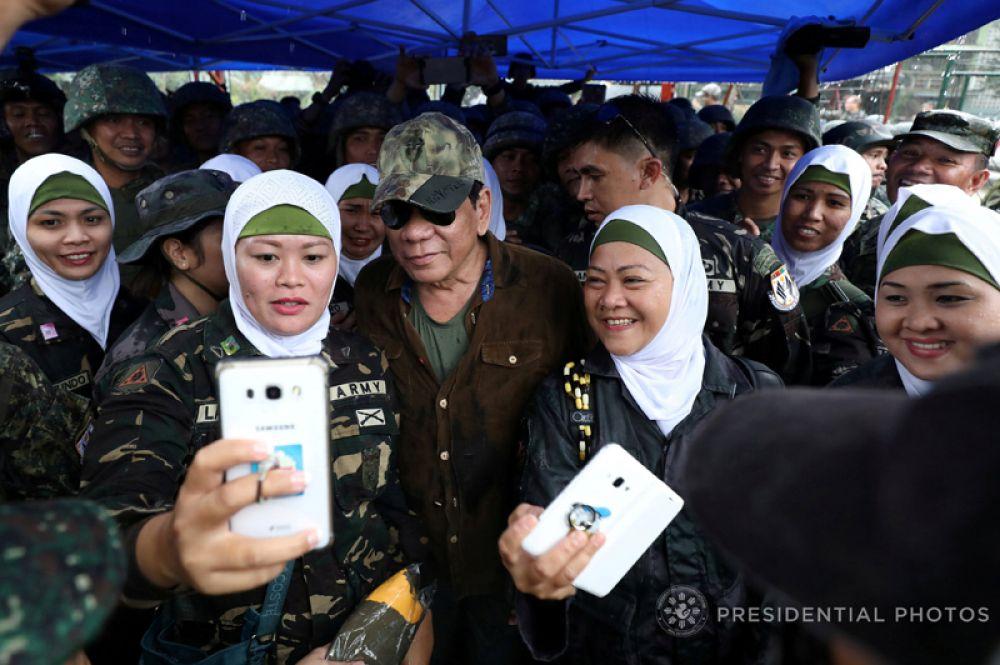 17 октября. Филиппинский президент Родриго Дутерте позирует для фото с женщинами-военнослужащими во время своего визита в Банголо, Марави, Филиппины.