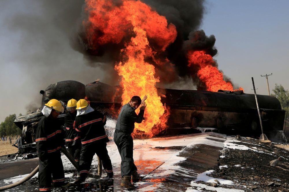 16 октября. Пожарные пытаются потушить горящий танкер с топливом, который загорелся после попадания бомбы, Джалалабад, Афганистан.