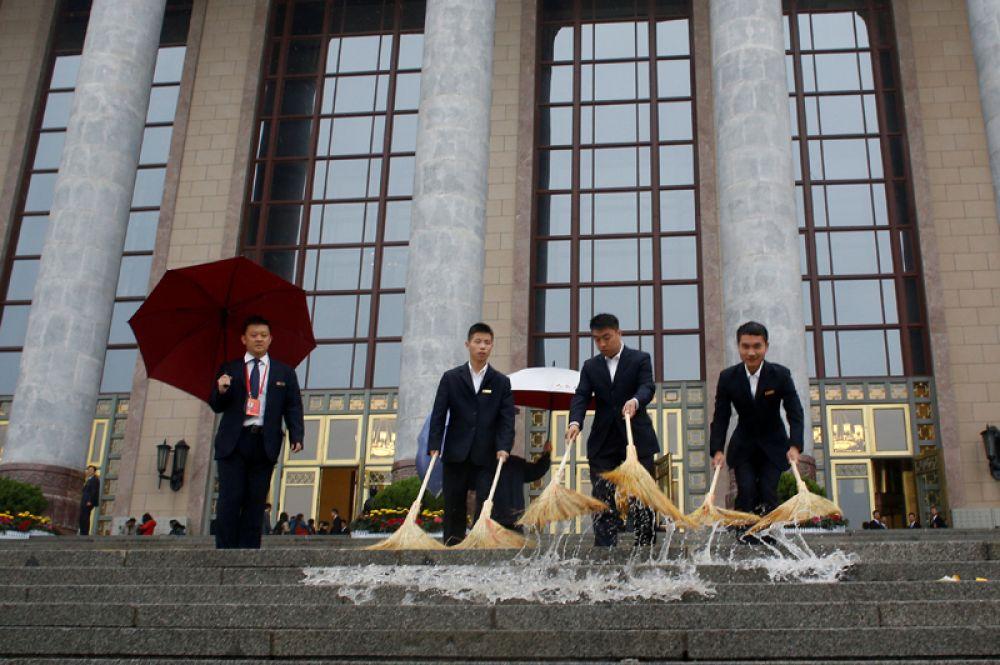 18 октября. Сотрудники службы безопасности чистят ступени Дома народных собраний перед открытием 19-го Национального конгресса Коммунистической партии Китая в Пекине.