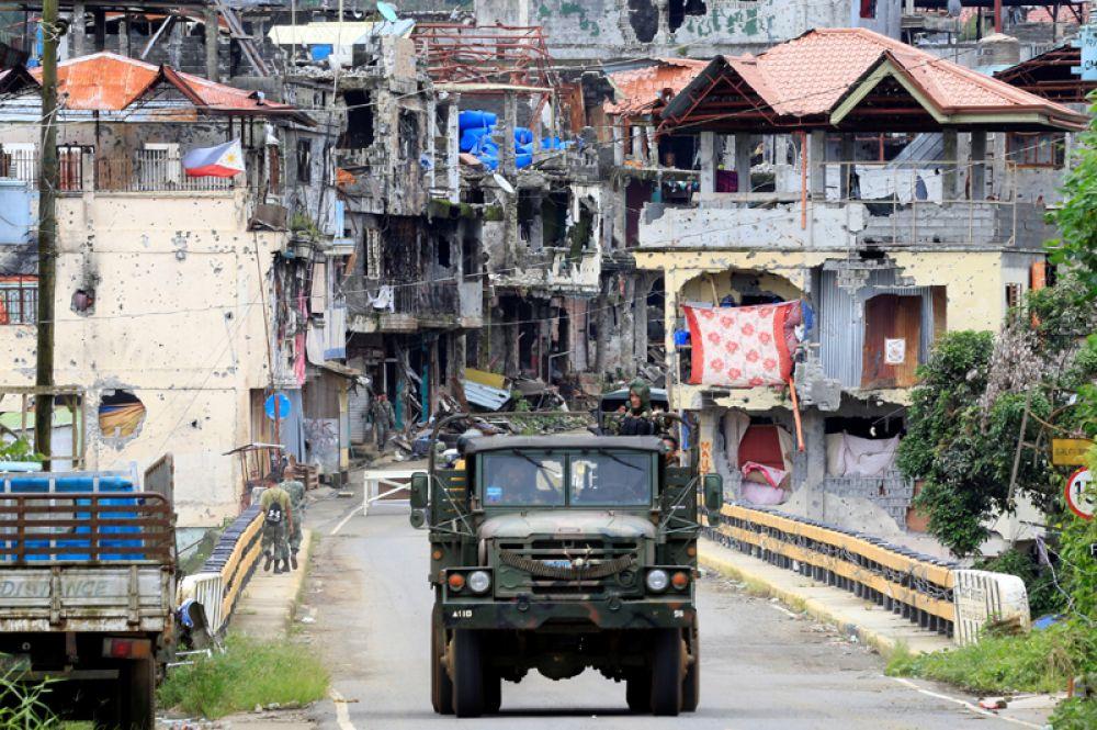 Солдаты на военном грузовике проезжают мимо повреждённых домов и зданий после того, как правительственные войска очистили территорию от боевиков в городе Марави.