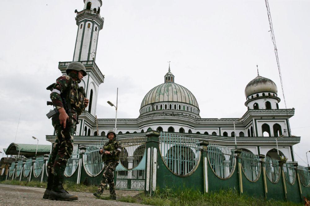 Солдаты правительственных войск стоят перед мечетью в Марави.