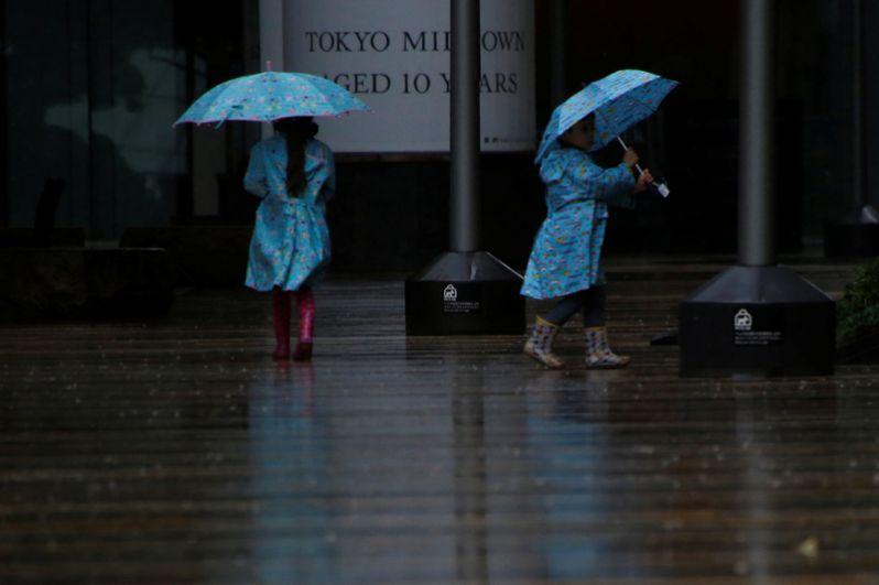 Дети гуляют под сильным дождем в Токио, в то время как тайфун «Лан» подходит к материковой части Японии.