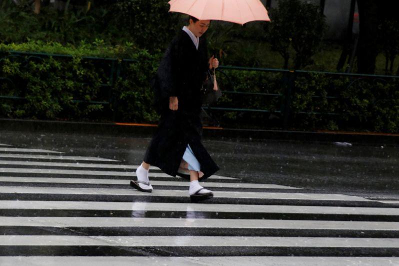 Женщина в кимоно переходит дорогу в сильный дождь, Токио.