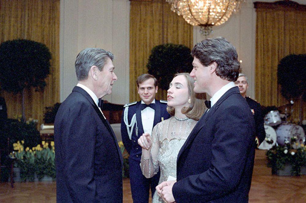 В 1978 году Билл Клинтон был избран губернатором Арканзаса. Будучи первой леди штата в течение двенадцати лет, Хиллари активно участвовала в общественной жизни штата, в частности, в таких областях, как образование, здравоохранение и защита прав детей. На фото: 1983 год. Президент Рональд Рейган с Биллом Клинтоном и Хиллари Клинтон на ужине в честь губернаторов штатов в Белого Дома.