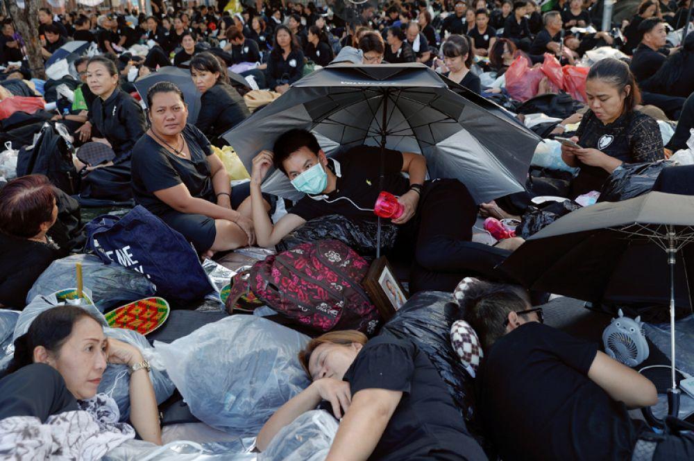 За сутки до кремации десятки тысяч тайцев собрались в историческом центре Бангкока, чтобы выразить почтение умершему королю. Одетые в черное горожане заняли все дороги и тротуары близ Большого королевского дворца.