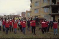 «Помоги, Максим! Руку протяни!..», - энергично отплясывают дольщики на фоне недостроенной многоэтажки на пр. Декабристов.