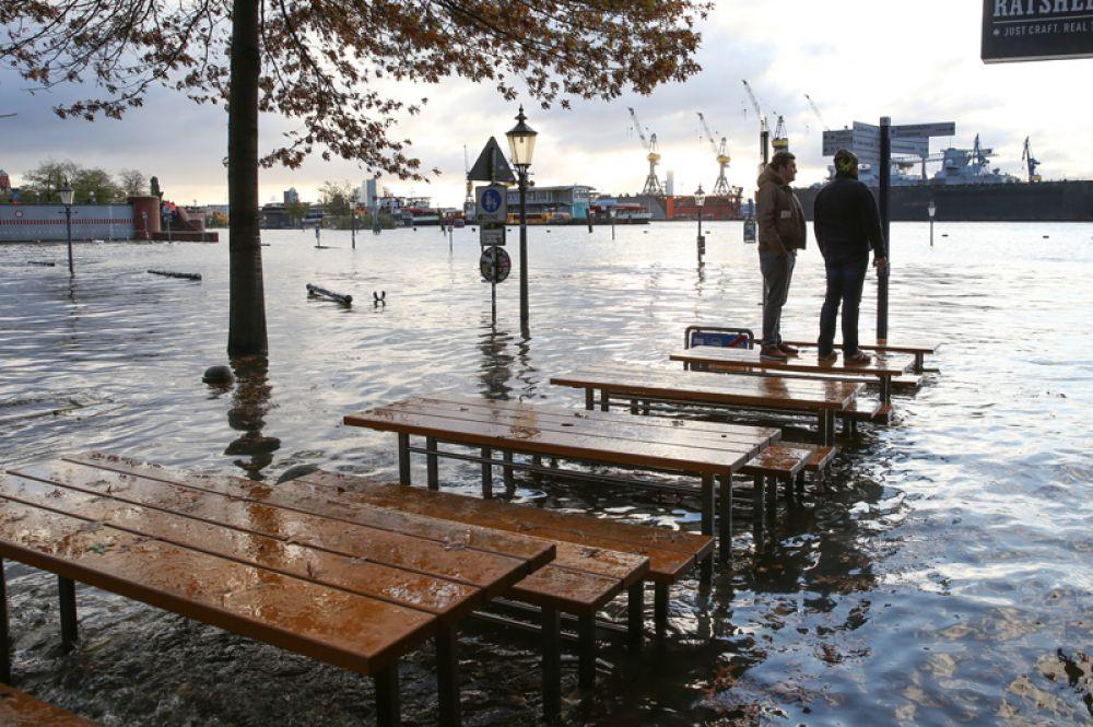 Люди стоят в столах на затопленном рыбном рынке в Гамбурге.