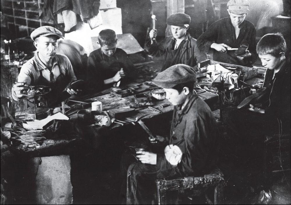 Бывшие беспризорные учатся сапожному делу в специально открытых мастерских, г. Николаев, 1931 год.