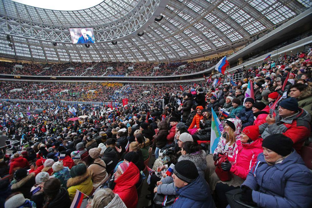 Зрители намитинге-концерте «Россия объединяет!» набольшой спортивной арене «Лужники» вМоскве.