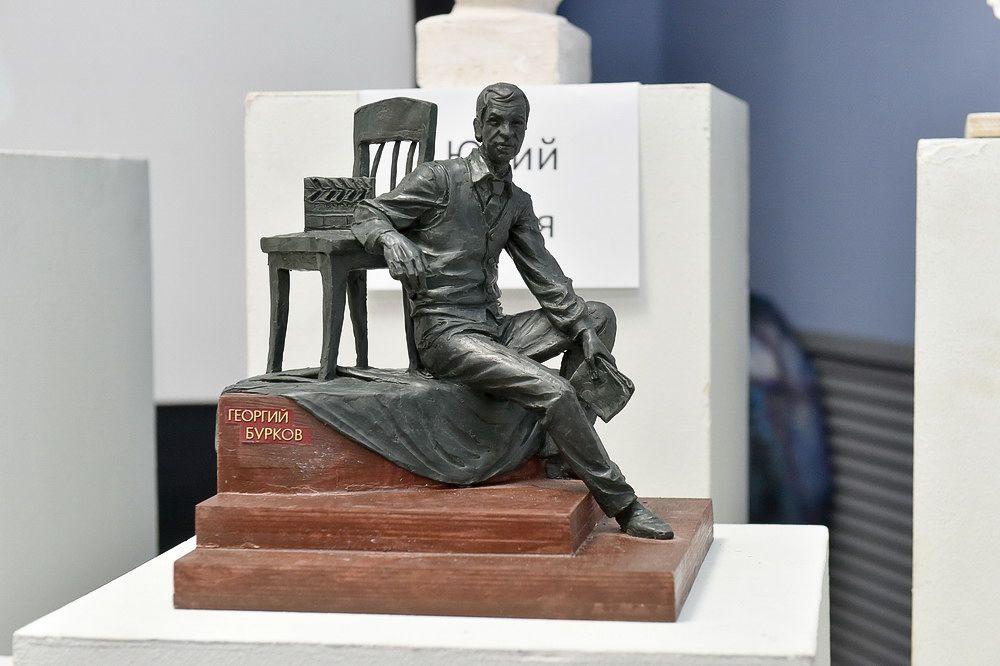 Юрий Злотя изобразил фигуру Георгия Буркова рядом со стулом с киношной хлопушкой.