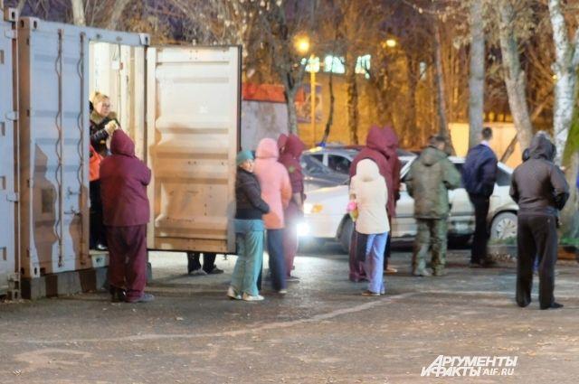 Эвакуированные сотрудники греются в ангаре, установленном за зданием торгового центра.