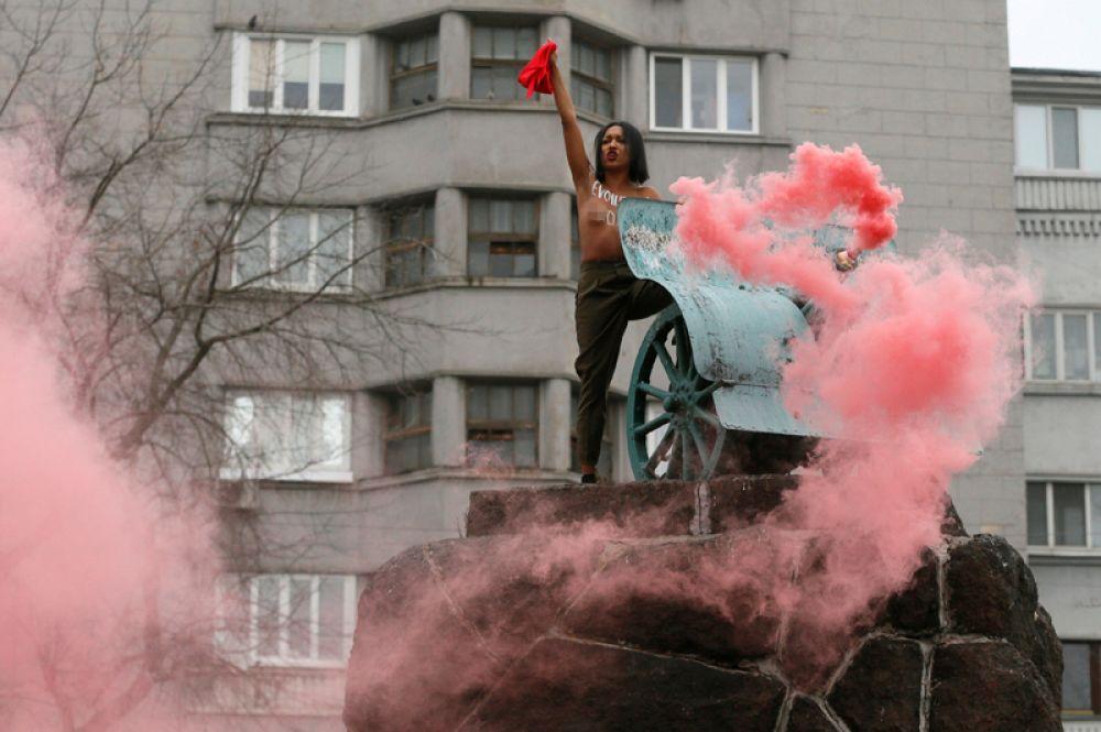 7 ноября. Активистка движения Femen выступает против деятельности президента Петра Порошенко и правительства Украины на памятнике героям Октябрьской революции в Киеве, Украина.