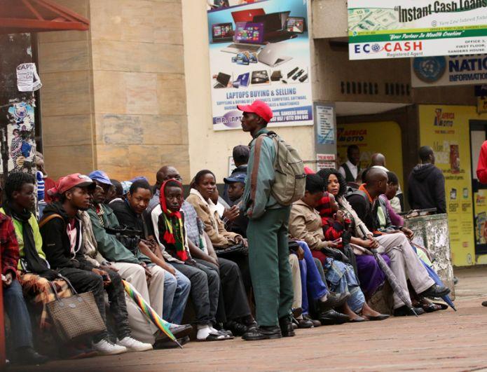 Местные жители стоят в очереди к банку, чтобы снять деньги.