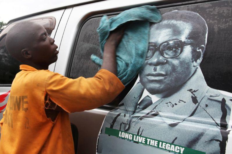 Местный житель моет машину с портретом президента Мугабе.