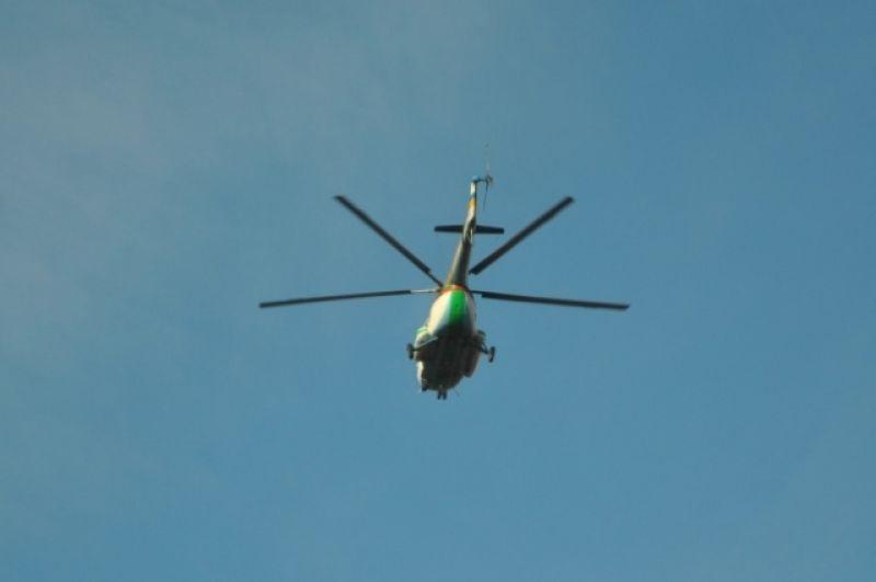На фото - военные с помощью вертолета досматривают территорию