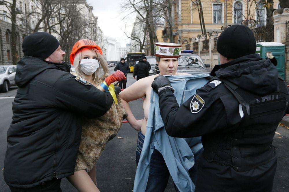 21 ноября. Полицейские задерживают активисток группы «Фемен» во время акции протеста против президента Украины Петра Порошенко возле штаб-квартиры президента в Киеве.