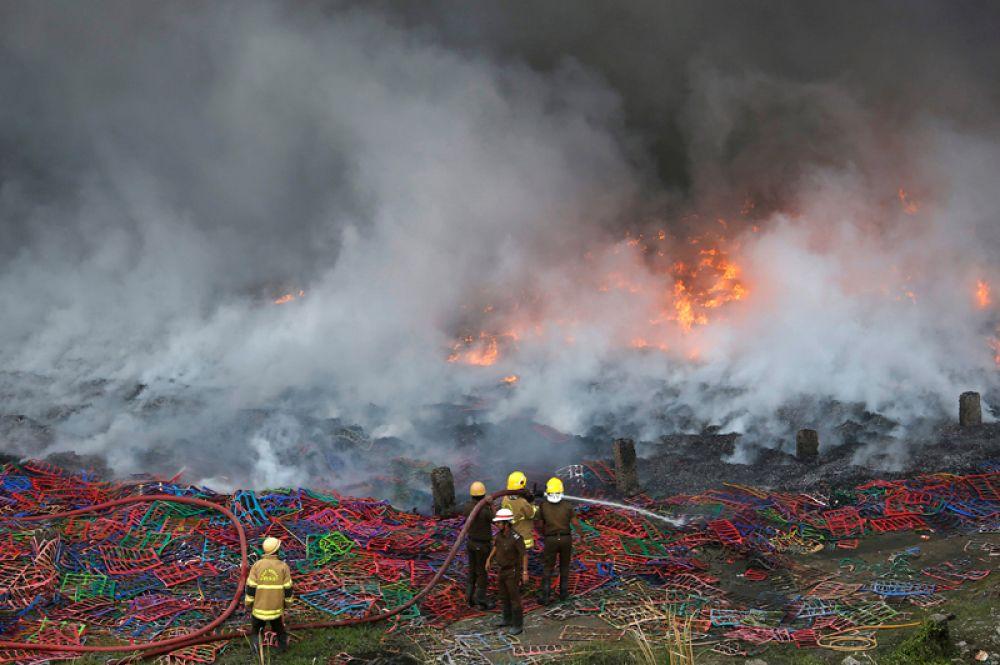 24 ноября. Пожарные пытаются потушить пожар, возникший на обувной фабрике в жилом районе Калькутты, Индия.