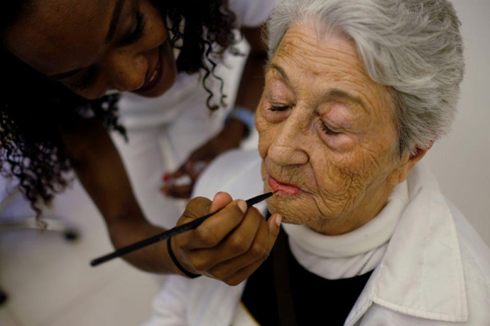 27 ноября. Пожилая женщина делает макияж в салоне красоты в Сан-Паулу, Бразилия, во время благотворительного мероприятия, организованного для женщин, которые живут в домах престарелых.