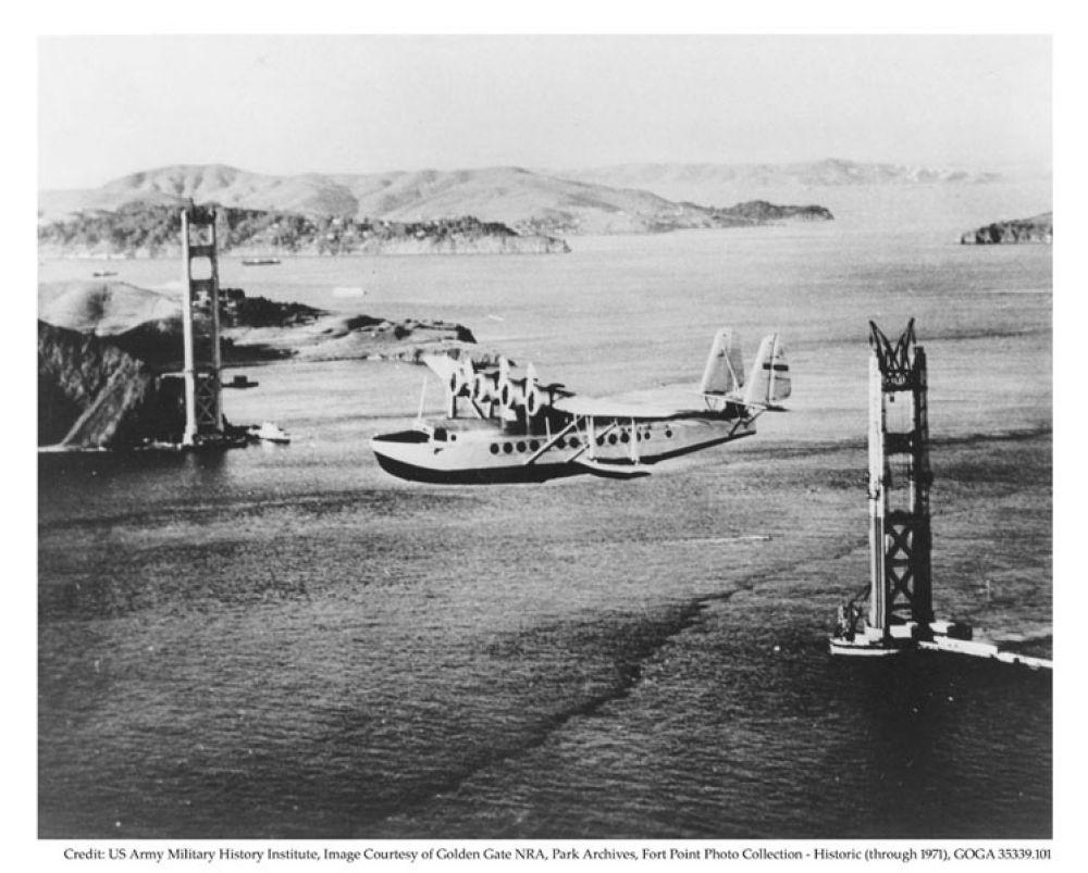 Самолет, пролетающий над мостом «Золотые ворота» во время его строительства. 1930-е годы.