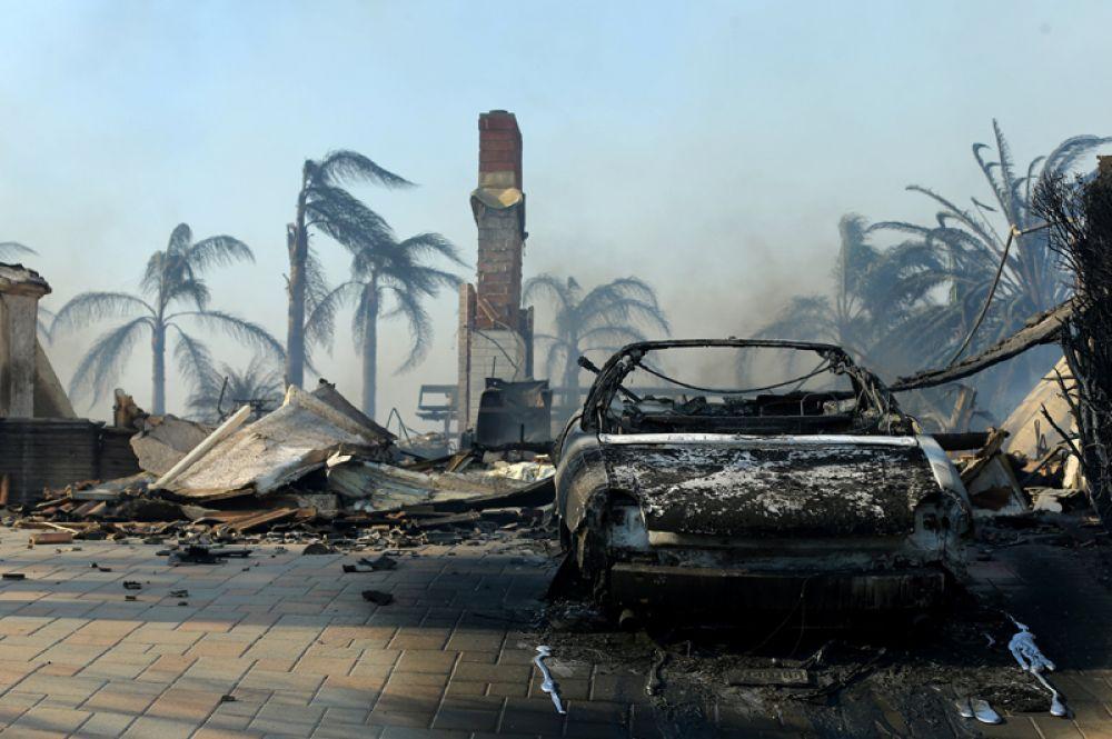 Руины дома и сгоревший автомобиль после пожара в Вентуре.