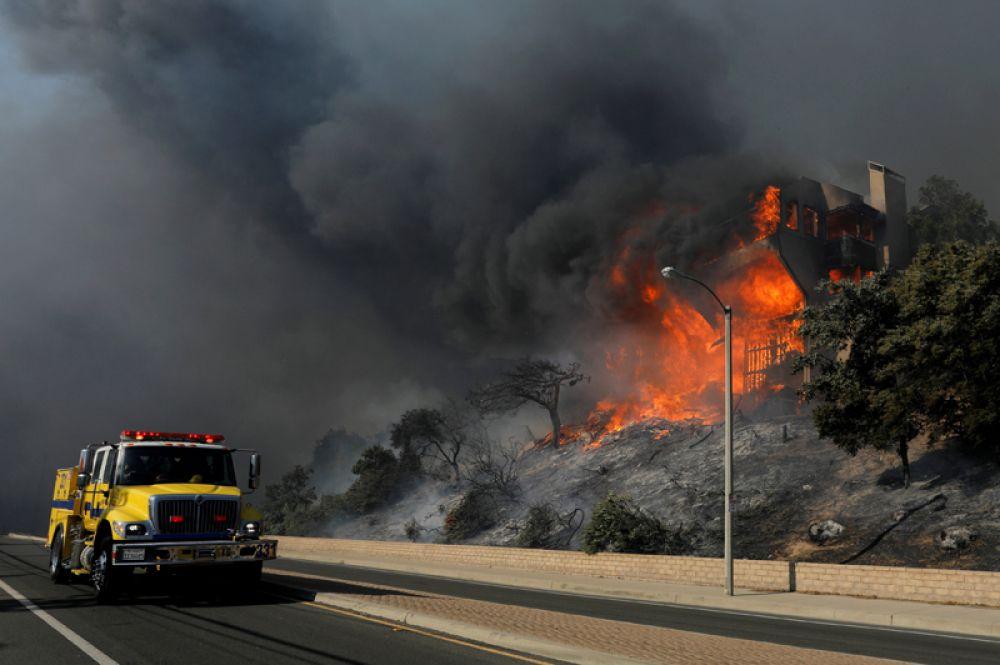 Пожарная машина проезжает мимо горящего дома в округе Вентура.