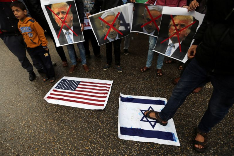 Палестинцы сжигают плакаты с изображением Нетаньяху и Трампа во время протеста против намерения США переместить свое посольство в Иерусалим и признать город Иерусалим столицей Израиля в Рафахе в южной части сектора Газа.