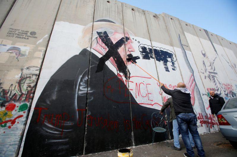 Мужчина закрашивает граффити, изображающее президента США Дональда Трампа, в Вифлееме.