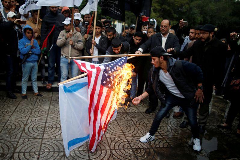 Палестинцы жгут израильский флаг и флаг США во время протестов в городе Газа.