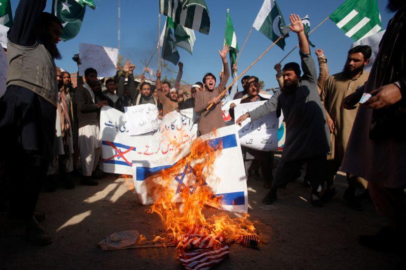 Демонстранты жгут флаги Израиля и США во время протеста в городе Пешавар, Пакистан.