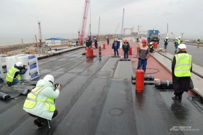 Журналисты фотографируют процесс гидроизоляции мостового полотна.