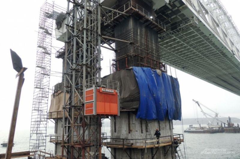 На стройке установили лифт, который поднимает людей на высоту арок.