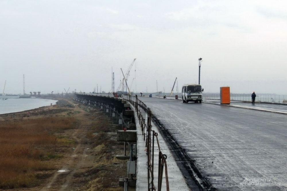 По готовой части автомобильного моста уже ездят вахтовые автобусы и другая техника строителей.