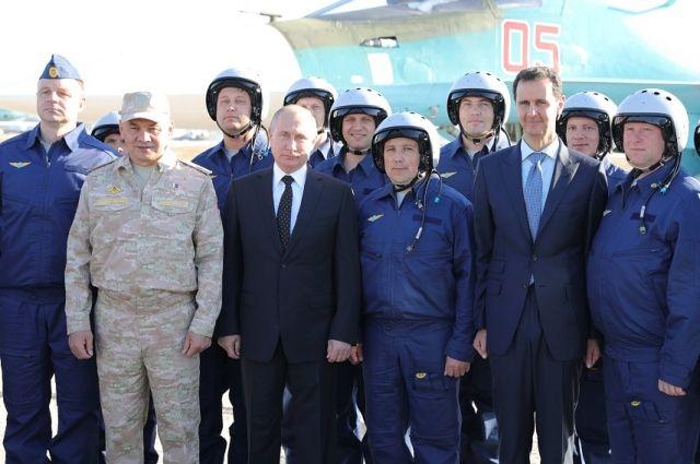 Сергей Шойгу, Владимир Путин и Башар Асад с российскими военнослужащими на авиабазе Хмеймим в Сирии.