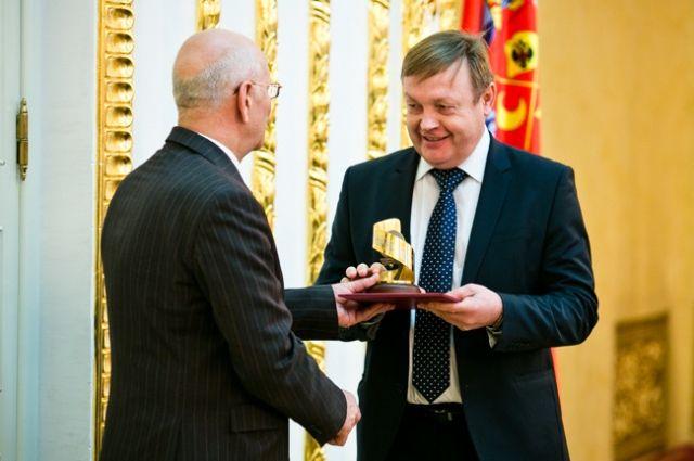 Губернатор Юрий Берг вручает награду начальнику финансового управления АО «Уральская Сталь» Андрею Дианову.