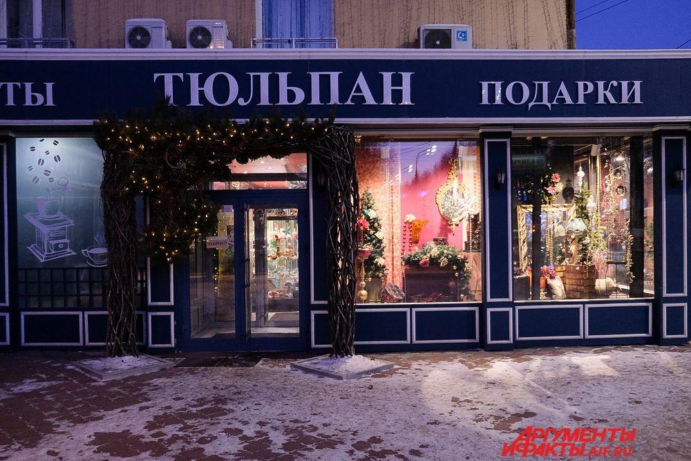 Новогодние витрины и праздничные вывески магазинов украшены нарядной атрибутикой.
