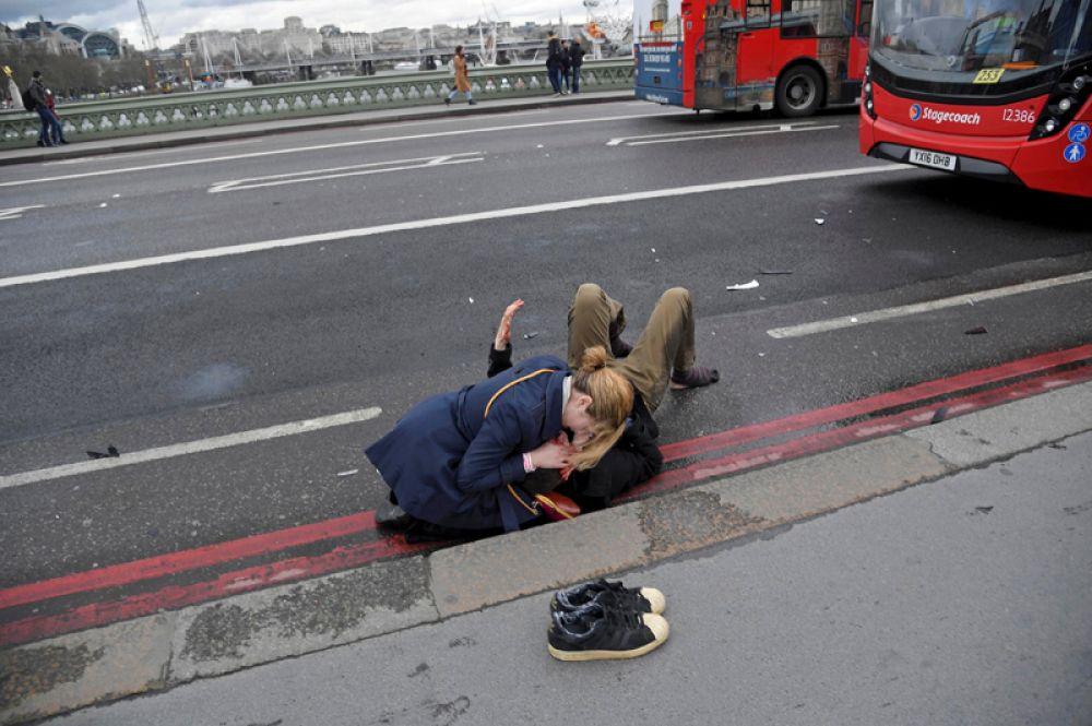 Женщина помогает пострадавшему после теракта на Вестминстерском мосту в Лондоне. Злоумышленник въехал в толпу людей, затем на полной скорости врезался в ограду британского парламента и ранил ножом полицейского. 22 марта 2017 года.