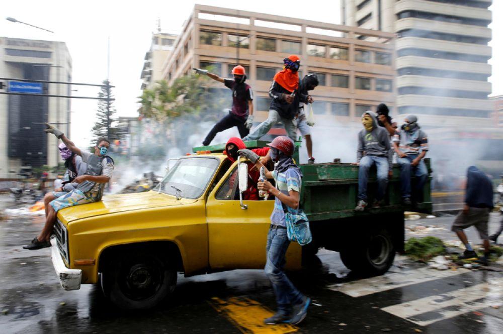 Демонстранты на грузовике во время митинга против президента Венесуэлы Николаса Мадуро в Каракасе. Причиной массовых выступлений стали решения Верховного суда, касающиеся расширения полномочий главы государства. 29 июня 2017 года.