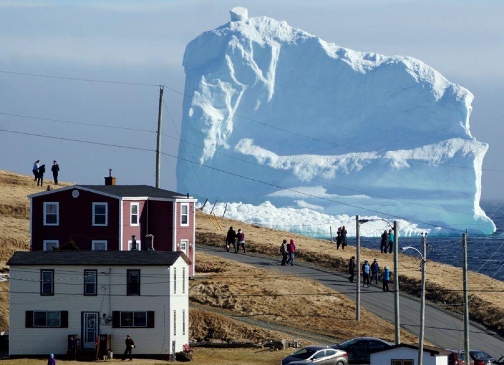 Гигантский айсберг проплывает мимо небольшой канадской деревни Ферриленд на острове Ньюфаундленд. 16 апреля 2017 года.