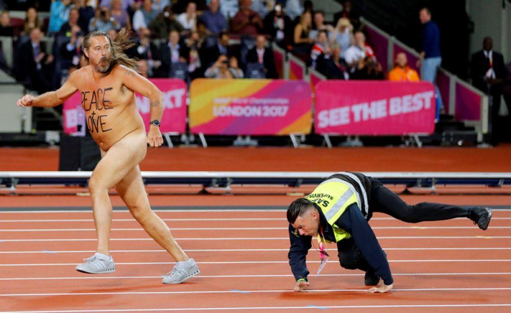 Обнаженный мужчина на дорожке стадиона перед началом забега на сто метров в финале чемпионата мира по легкой атлетике в Лондоне. 6 августа 2017 года.