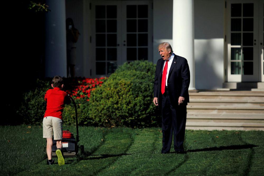 Президент США Дональд Трамп приветствует 11-летнего Фрэнка Гьяччо, когда тот косит траву в Розовом саду Белого дома в Вашингтоне. Мальчик написал Трампу письмо с предложением подстригать газон и был принят на эту работу на один день. 15 сентября 2017 года.