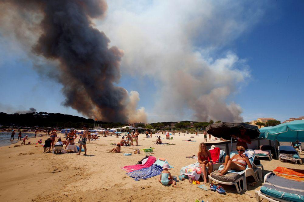 Туристы отдыхают на пляже курорта Борм-ле-Мимоза, в то время как в регионе бушуют лесные пожары, Франция. 26 июля 2017 года.