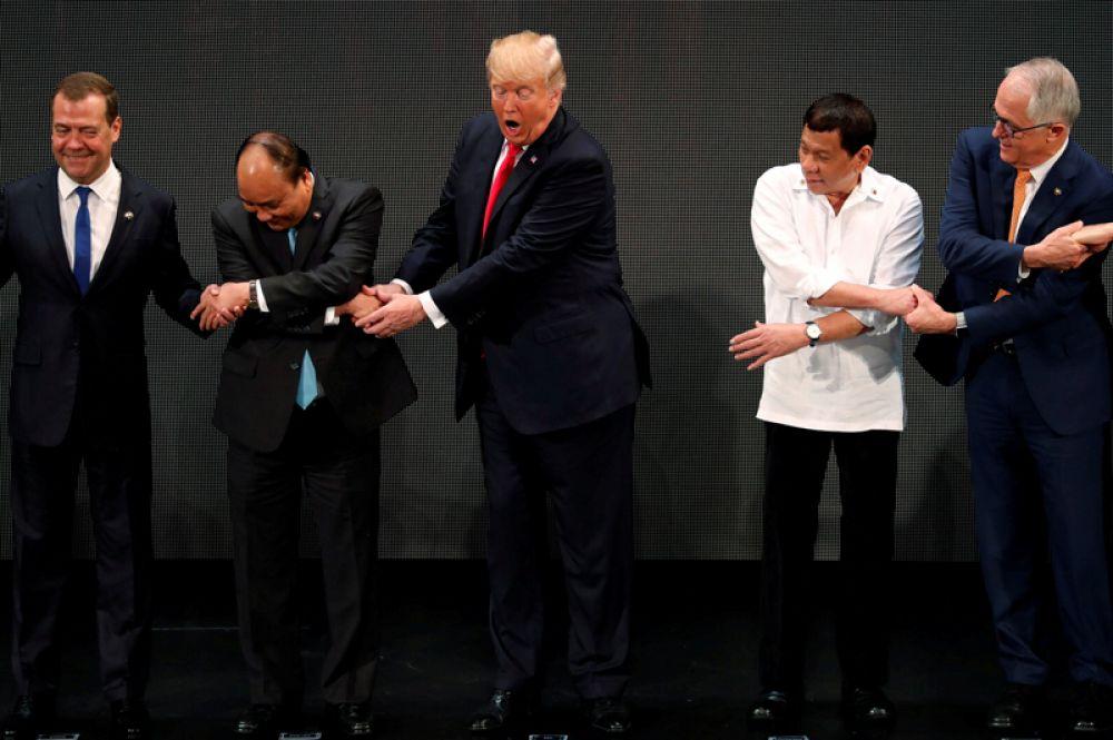 Традиционное рукопожатие на саммите АСЕАН. Дональд Трамп не сразу понял, что от него требуется, а Дмитрий Медведев не стал скрещивать руки во время фотографирования. 12 ноября 2017 года.