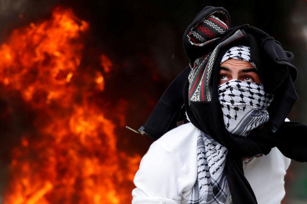 Участник протестов против решения президента США Дональда Трампа признать Иерусалим столицей Израиля возле города Рамалла на западном берегу реки Иордан, 20 декабря 2017 года.